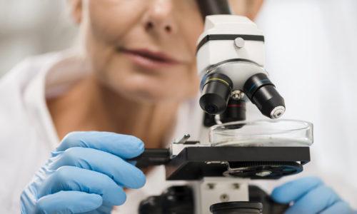defocused-female-scientist-looking-through-microscope